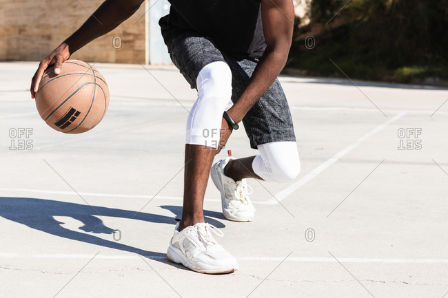 Cropped unrecognizable African American male athlete playing basketball on court in summer and looking at camera