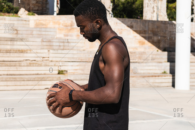 Side view of fit African American male standing on basketball court with ball and looking away