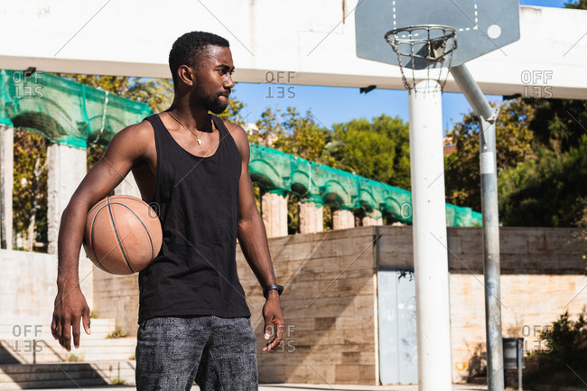 Fit African American male standing on basketball court with ball and looking away