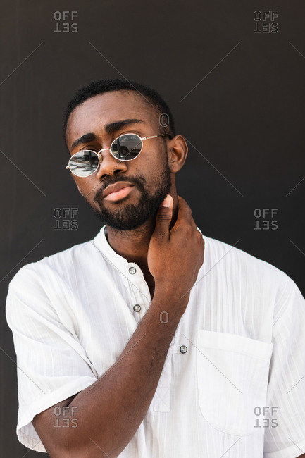 Confident African American male wearing stylish sunglasses and white t shirt standing on street while looking at camera and touching neck