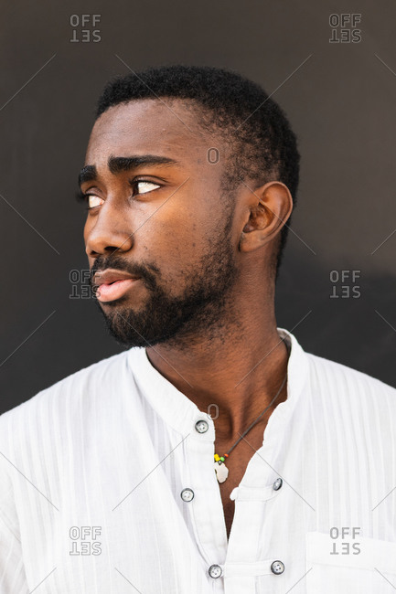 Confident African American male wearing white t shirt standing on street while looking away