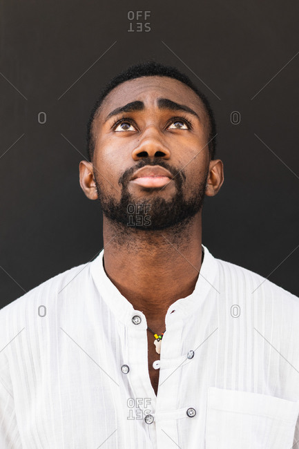 Confident African American male wearing white t shirt standing on street while looking up