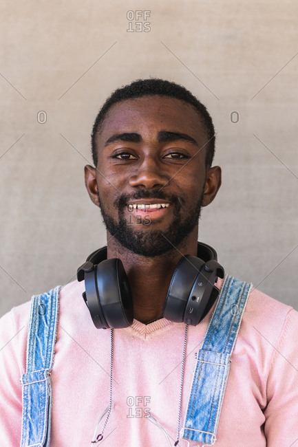 Cheerful African American male hipster in trendy clothes and with headphones on neck standing against concrete wall and looking at camera