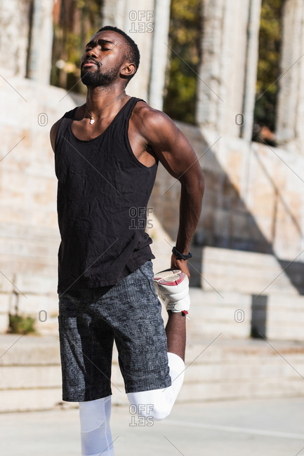 Fit African American male basketball player warming up stretching legs while preparing for training on sports ground in summer with eyes closed