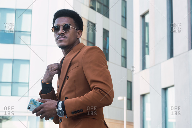 Cheerful young African American businessman in stylish suit and eyeglasses walking in office corridor with cup of takeaway coffee and smartphone during break