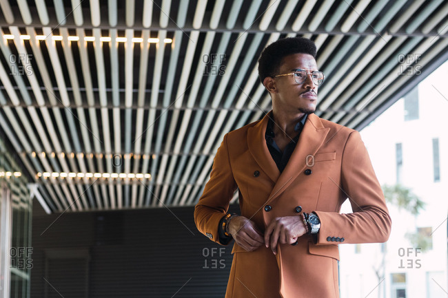 Self assured African American male wearing stylish jacket and sunglasses while standing in city and looking away