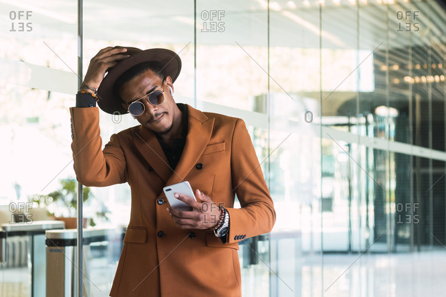 Front view of young handsome black guy in trendy suit and sunglasses adjusting hat while standing in modern building hall with smartphone in hand
