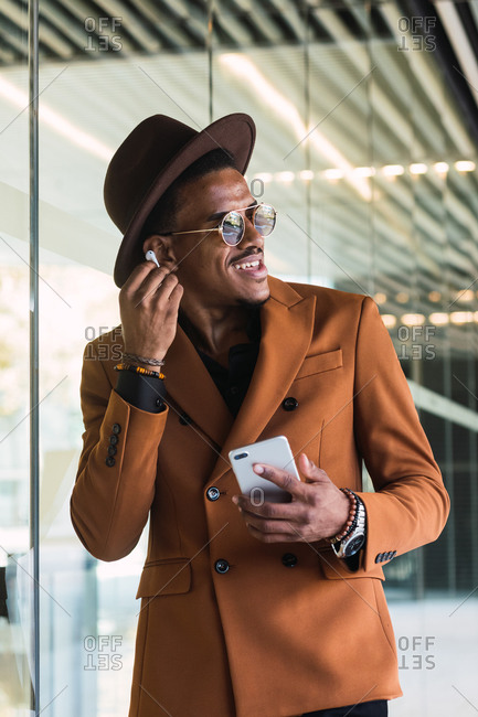 Positive young African American man in stylish suit and hat smiling while having phone conversation using wireless earphones and looking away in modern building with glass walls