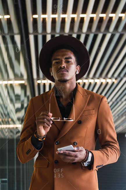 Young handsome black guy in trendy suit and sunglasses adjusting hat and smiling while standing in modern building hall with smartphone hand