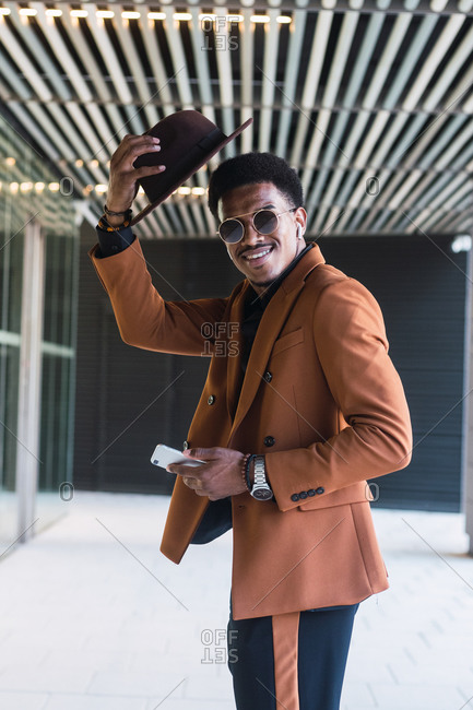 Side view of young handsome black guy in trendy suit and sunglasses adjusting hat and smiling while standing in modern building hall with smartphone in hand