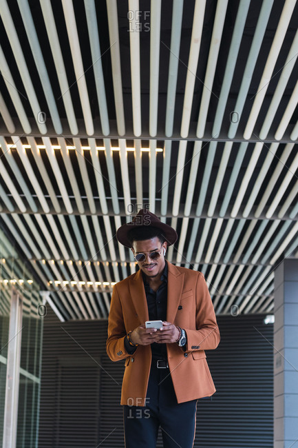 Young handsome black guy in trendy suit and sunglasses adjusting hat and smiling while standing in modern building hall with smartphone in hand