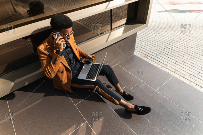 From above of concentrated young African American male freelancer in trendy suit and  sunglasses talking on smartphone and working on laptop while sitting on building stairs on street
