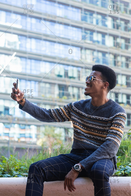 Cheerful young ethnic guy in stylish clothes and sunglasses relaxing on bench in city park and taking self portrait on smartphone