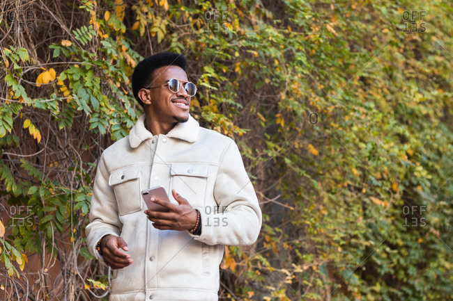 Low angle of happy young African American guy in trendy jacket and sunglasses smiling and looking away while using smartphone in autumn park