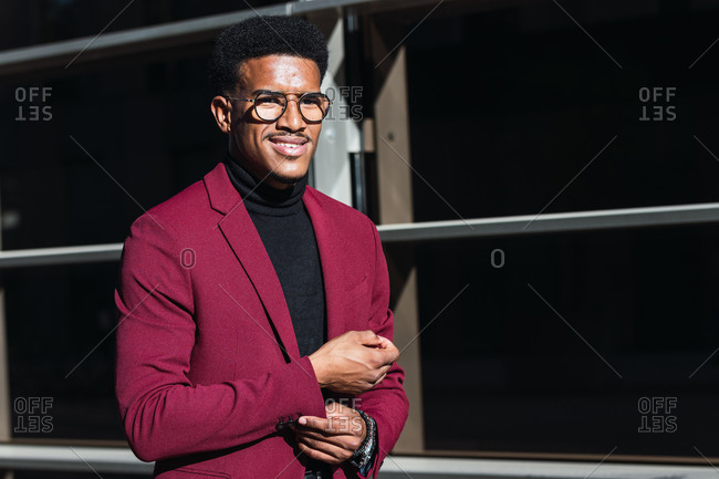 Confident young African American male in fashionable suit and eyeglasses standing on street near modern building with glass walls on sunny day