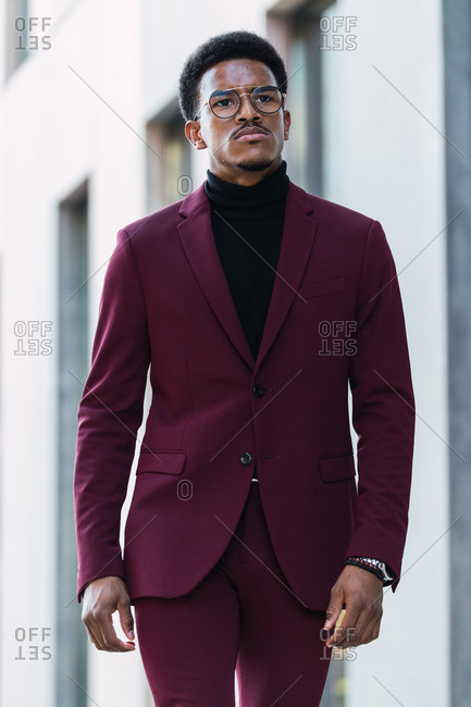 Cheerful young African American businessman in stylish suit and eyeglasses walking in street