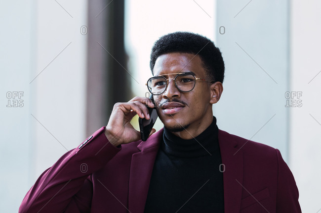 Serious young African American male manager in stylish suit and eyeglasses discussing business issues on smartphone and looking away