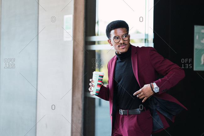 Side view of self assured young ethnic male entrepreneur in fashionable suit and eyeglasses drinking coffee from disposable cup during break on street
