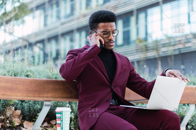Pensive young African American male freelancer in stylish outfit and eyeglasses sitting on bench in city park and having phone conversation during remote work on laptop