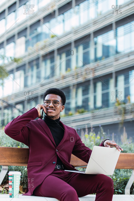 Happy young African American male freelancer in stylish outfit and eyeglasses sitting on bench in city park and having phone conversation during remote work on laptop