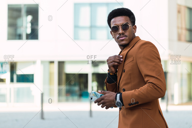Self assured African American male wearing stylish jacket and sunglasses adjusting collar of shirt while standing in city and looking at camera