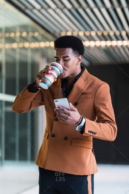 Low angle of cheerful young African American businessman in stylish suit and eyeglasses walking in office corridor with cup of takeaway coffee and smartphone during break