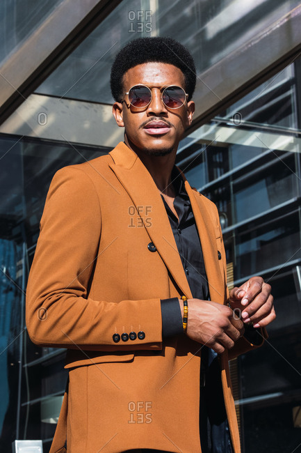 Confident young African American male entrepreneur in stylish suit and sunglasses standing on street near modern skyscraper with hand in pocket and looking away on sunny day