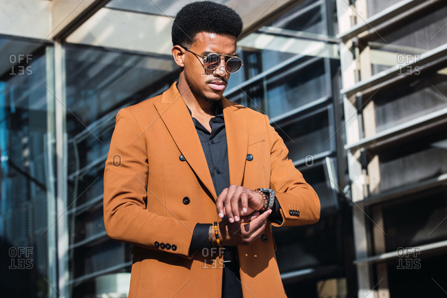 Stylish young African American businessman in fashionable suit and hat and checking time on wristwatch while waiting for meeting near contemporary skyscraper