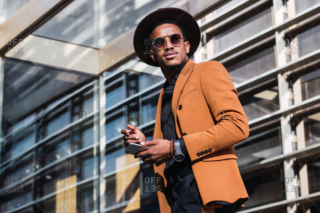 Content African American male in trendy hat and clothes walking along urban street and browsing mobile phone