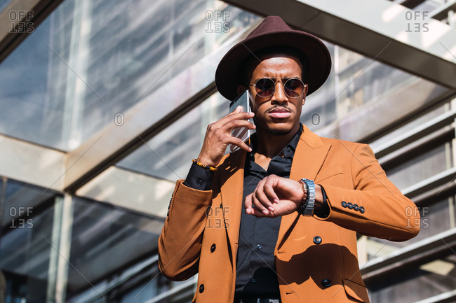 Low angle of stylish young African American businessman in fashionable suit and hat talking on smartphone and checking time on wristwatch while waiting for meeting near contemporary skyscraper
