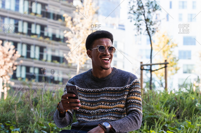 Optimistic African American male in cozy knitted sweater sitting on street with smartphone and laughing while looking away