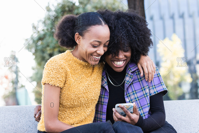 Happy young African American female friends hugging and laughing while sitting on bench and watching funny video on smartphone together on city street