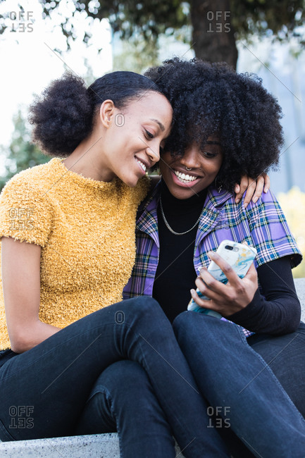 Cheerful young African American female friends hugging and taking selfie on mobile phone while spending time together on the street