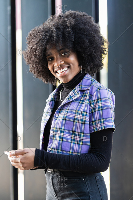 Happy young curly haired African American female in stylish casual outfit browsing smartphone while standing near wall of urban building on street looking at camera