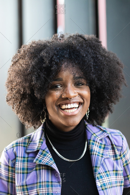 Modern young cheerful African American female with curly hair and piercing dressed in stylish checkered jacket looking at camera