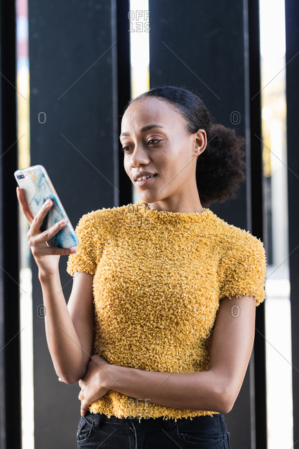 Young African American female looking away thoughtfully while browsing on mobile phone