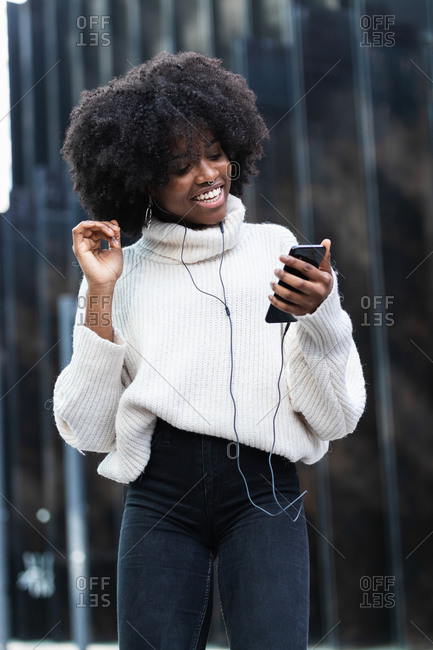 Optimistic young curly haired African American female student in stylish casual outfit using smartphone and listening to favorite song with earphones while standing on urban street