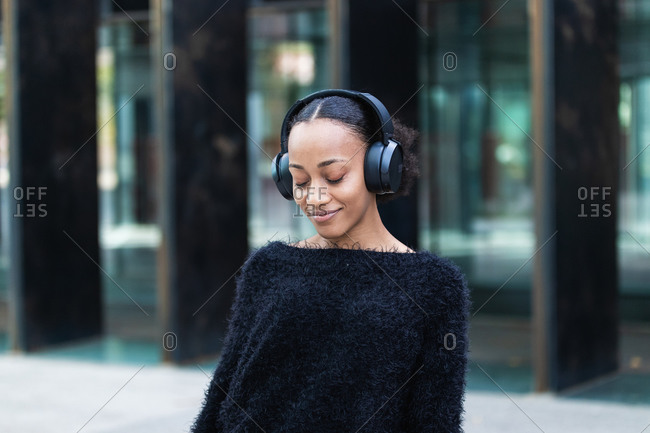 Happy calm young African American female in wireless headphones enjoying music on city street with eyes closed