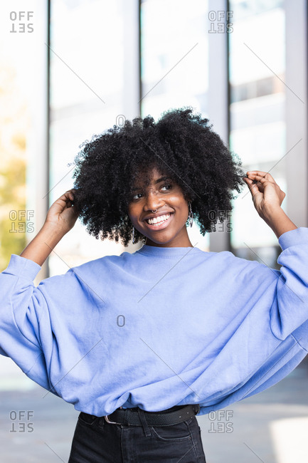 Cheerful young African American female with curly hair looking at camera while standing on the street