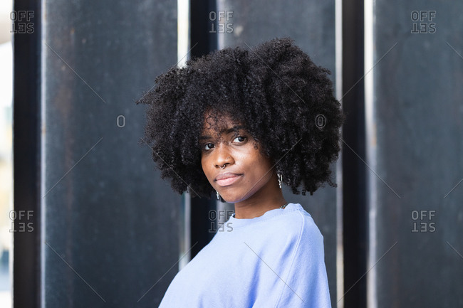 Beautiful young African American female with curly hair looking at camera while standing on the street