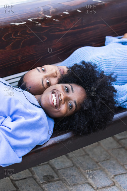 From above of optimistic young African American female friends lying face to face and listening to music with earphones while enjoying free time together