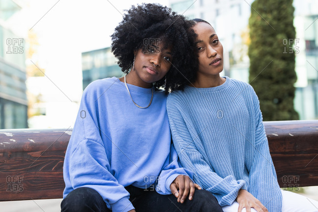 Young African American female friends with curly hair wearing similar lilac clothes cuddling together while resting on bench on urban street