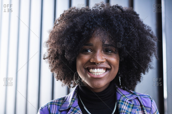 Delighted young black curly haired female with piercing in nose wearing stylish outfit and accessories smiling brightly while standing against blurred wall