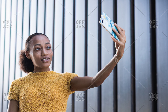 Confident smiling millennial African American female in stylish casual wear taking selfie on mobile phone while standing against wall of modern building