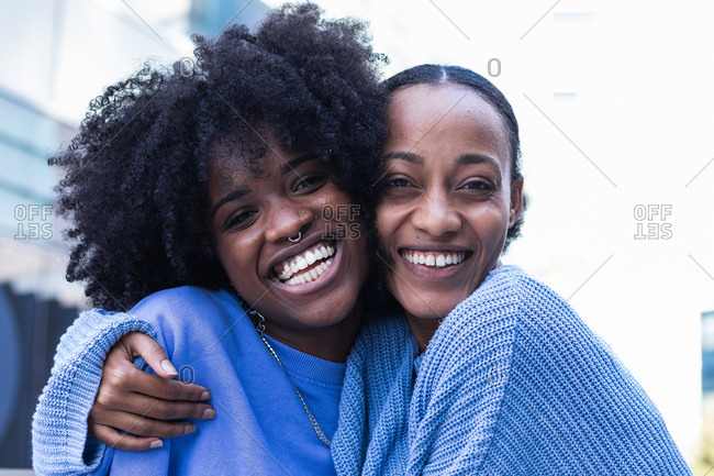 Cheerful young African American female friends with curly hair wearing similar lilac clothes cuddling together while resting on bench on urban street
