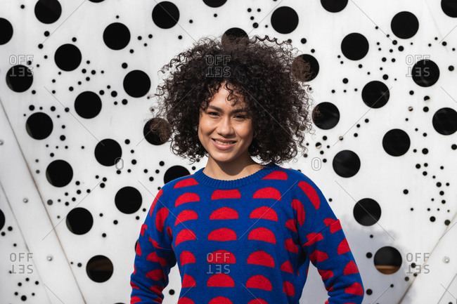 Delighted African American female in vivid sweater standing in urban area in city and looking at camera