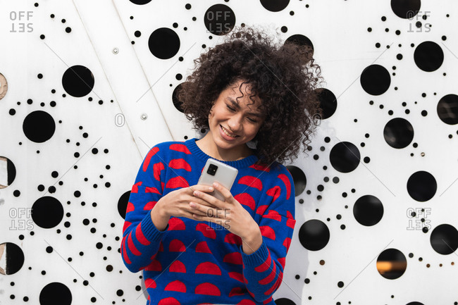 Positive African American female with curly hair and in stylish clothes standing in modern urban district and messaging on smartphone