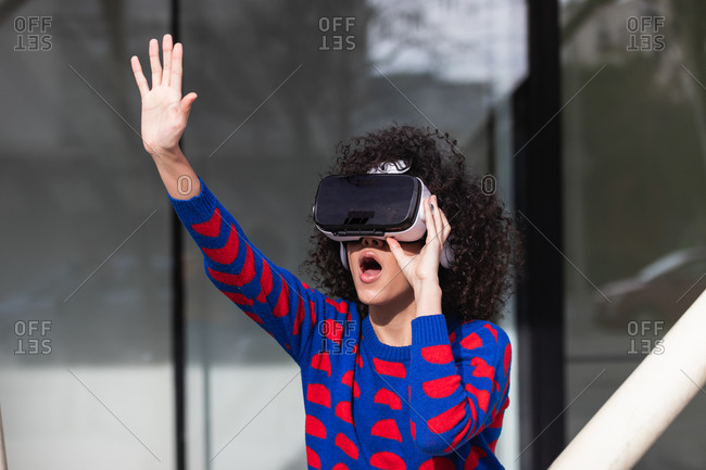 Astonished African American female in VR goggles experiencing virtual reality and touching air while standing on street