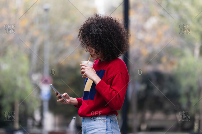 Charming African American female with curly hair and in stylish outfit taking selfie with plastic cup of fresh juice to go while using smartphone on street