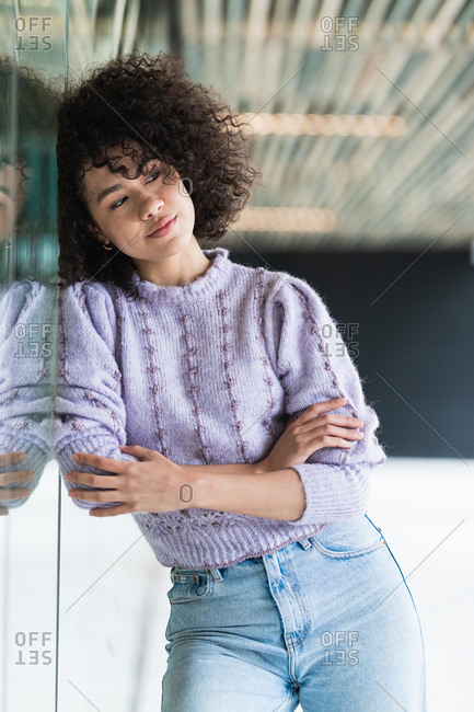 Thoughtful African American female with curly hair standing with crossed arms near glass building and looking away